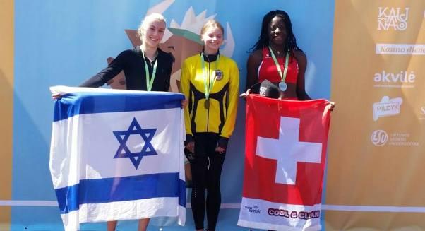 צ'יינוב (משמאל) מציגה בגאווה את הדגל ואת המדליה בליטא (צילום מתוך דף הפייסבוק)
